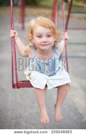 Joyful redheaded child swinging on a swing