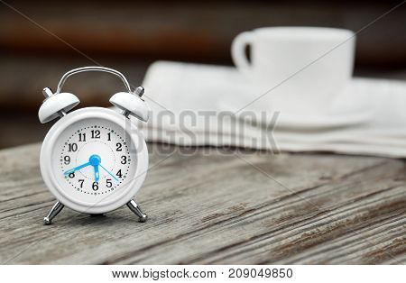 Alarm clock on wooden bench outdoors. Morning routine concept