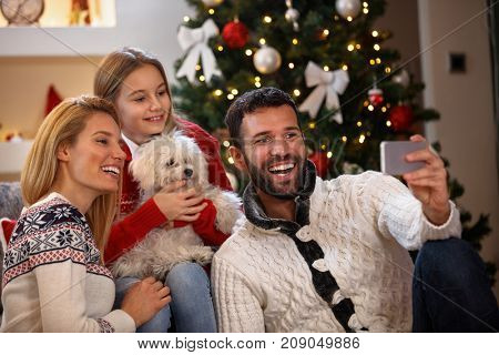 Happy family making a Christmas Selfie with a smart phone