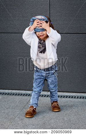 fashion baby girl hip hop.Portrait of a cute little girl in fashionable clothes.model child hip-hop.little baby girl in the baseball cap happy dancing in the background of the gray wall.