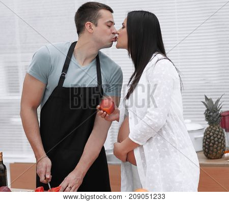 pregnant couple kissing while standing in the kitchen.