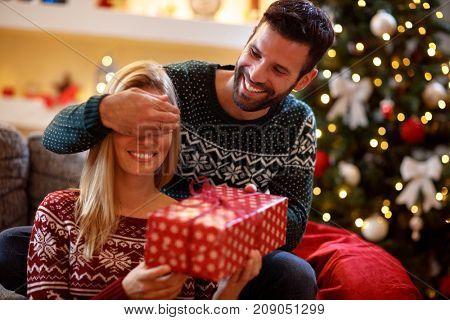 Guy covering his smiling girlfriend's eyes while giving her present