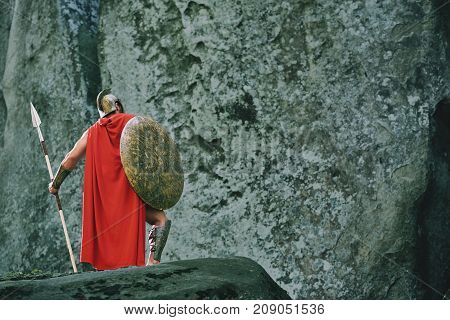 Full length rearview shot of a medieval warrior in a red cloak standing near rocky mountain holding a spear copyspace.
