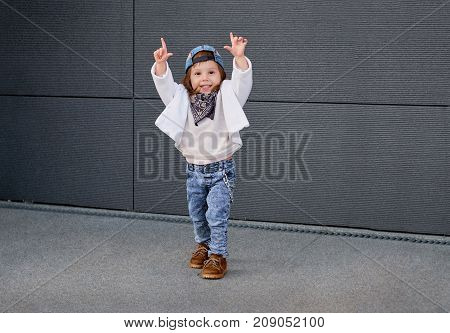 fashion baby girl hip hop.Portrait of a cute little girl in fashionable clothes.little baby girl in the baseball cap happy dancing in the background of the gray wall. child waving his hands.
