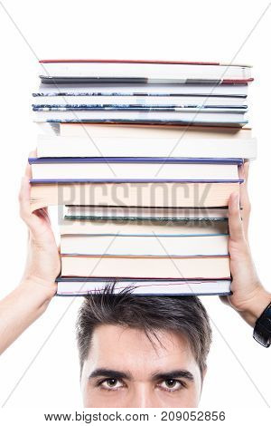 Close-up Of Student Holding Pile Of Books Over His Head