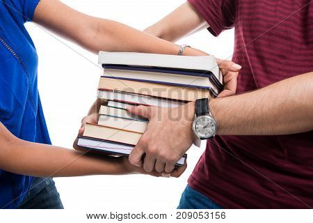 Close-up Of Students Pulling Pile Of Books