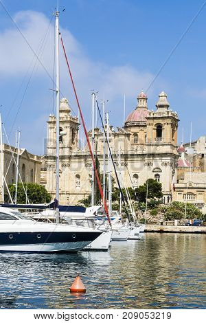 Yachts docked at the port of Malta. Boats moored in a row on the background of cathedral