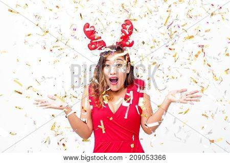 Amazed young woman under confetti rain shrugging shoulders and looking at camera. Cheerful beautiful lady in reindeer antler headband having fun at party. Winning concept