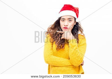 Arrogant confident young woman looking at camera and rubbing chin. Concentrated lady in santa hat taking decision. Making choice concept