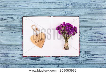 An open diary a wooden heart and flowers. Romantic concept. Wood valentine
