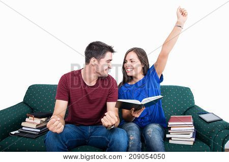 Student Couple Sitting On Couch Making Victory Gesture