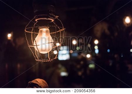 Close up old light bulb with surrounding ropes in dark place. Retro style with bokeh background