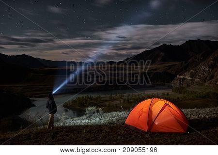 Male tourist with flashlight near his camp tent at night. Orange illuminated tent.