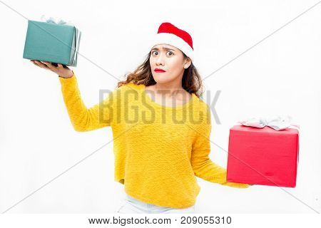 Confused attractive girl in Santa hat holding two boxes in hands while weighting Christmas gift and looking at camera. Misunderstanding woman thinking of benefit. Christmas shopping concept