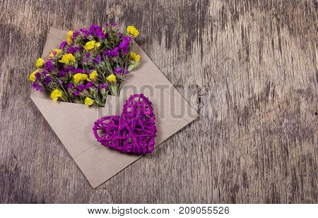 Pink heart and romantic letter. Flowers in the envelope. Wicker Valentine
