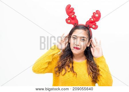 Distrustful girl in antler headband not believing in her ears and listening. Pretty young woman looking at camera. News or gossips concept