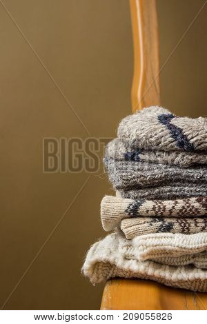 Stack of Handmade Warm Knitted Socks Scarfs Mittens Sweaters From Rough Wool Yarn Brown Beige Grey on Vintage Chair Golden Olive Color Wall Background. Eco Fashion Kinfolk Style. Interior