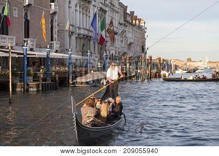 VENICE ITALY-SEPTEMBER 23 2017: Venetian gondolier rowing through the Grand Canal. Gondola is iconic traditional boat very popular means of transport for tourists