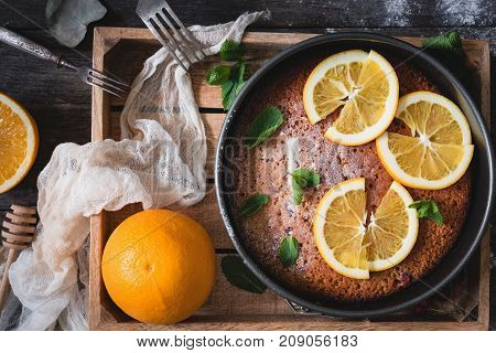 Orange cake decorated with orange slices and mint leaf on wooden tray. Top view. Food still life