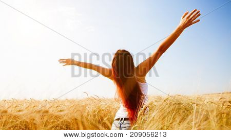 Girl with raised hands on wheat field