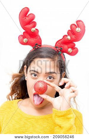 Grimacing funny girl sticking out tongue and hiding nose behind Christmas ball. Expressing young woman in costume. Mischief concept