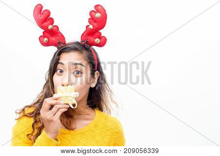 Grimacing pretty woman covering mouth behind gift box and looking at camera. Funny expressing young lady in reindeer antler headband preparing surprise. Christmas concept