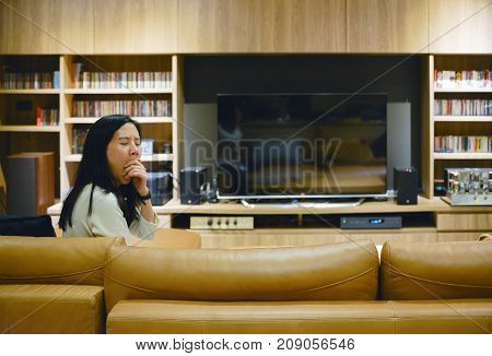 Asian Woman Yawning In Front Of Blank Screen Tv In Living Room At Night