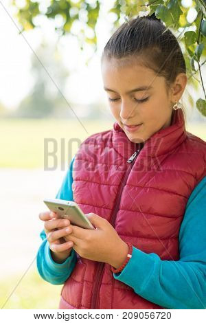 Beautiful girl talking on a smartphone in red vest on the outdoor.Handsome smiling girl with mobile phone walking on outdoor. Portrait smiles girl. copy space.