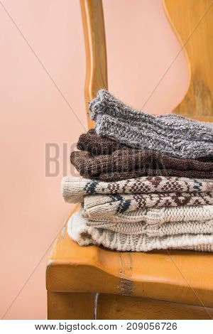 Stack of Handmade Warm Knitted Socks Scarfs Mittens Sweaters From Rough Wool Yarn Brown Beige Grey on Vintage Chair Trendy Peach Color Wall Background. Eco Fashion Kinfolk Style. Interior