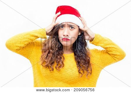 Offended young woman in Santa hat pouting and looking at camera. Portrait of unhappy girl with curly hair worried about Christmas party. Sad before Christmas concept