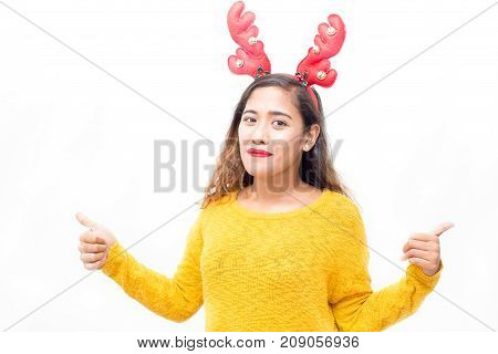 Pleased pretty woman in headband showing thumbs up and looking at camera. Cheerful attractive girl recommending good Christmas item. Approval concept