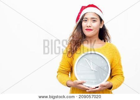 Positive charming woman waiting for New Year and holding watch. Pretty student girl in Santa hat valuing time. 5 minute before New Year concept