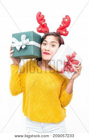Positive pretty girl enjoying Christmas time and showing her presents. Smiling happy young woman in reindeer antler headband looking at camera and enjoying buying gifts. New Years eve concept