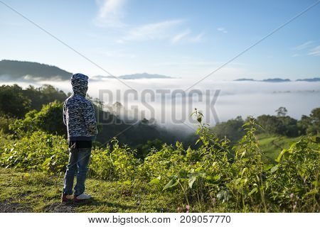 Young boy traveler looking sea of mist on the morning light.