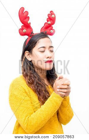 Serene beautiful young woman in reindeer antler headband praying with closed eyes and touched palms before Christmas. Calm girl concentrated on her wish. Waiting for miracle concept