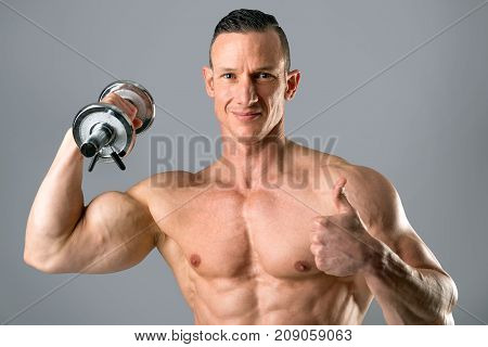 man with powerful body and biceps using dumbbell