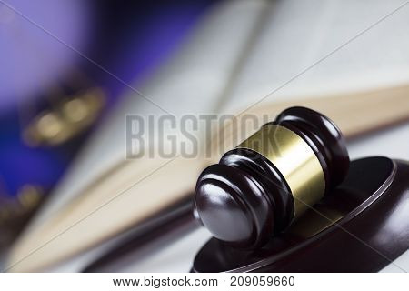 Gavel, book and scales on bokeh background.