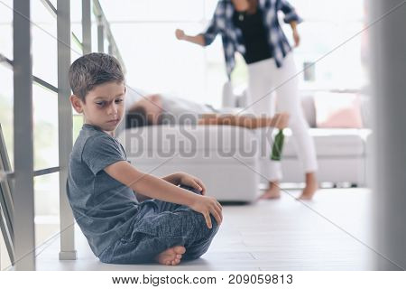 Little boy with bruise sitting on floor while his parents fighting on background. Domestic violence concept