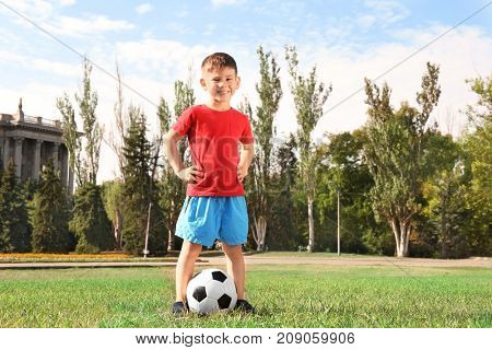 Cute boy with soccer ball on lawn