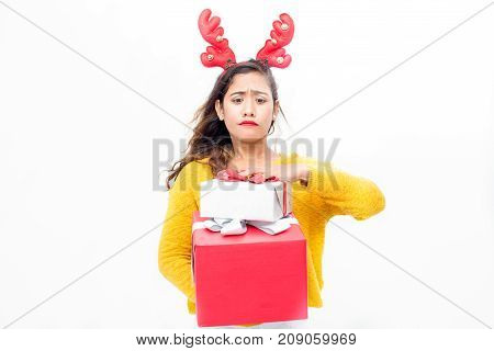 Uncertain responsible young woman carrying Christmas presents and trying to not drop them. Funny grimacing lady buying gifts. New year eve concept
