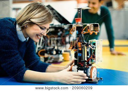 Young beautiful engineer testing her robot in workshop