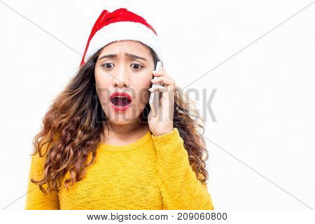 Upset girl in santa hat getting bad news on phone. Shocked young woman with curly hair talking on phone against white background. Failure concept