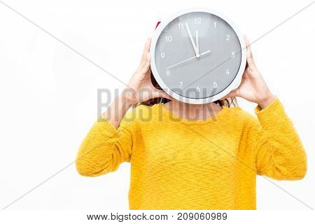 Woman covering face with watch showing time before New Year. Girl in yellow sweater holding watch while waiting to finish sales. Time is running out concept