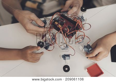 Close up. The guy collects a spider robot with two little boys. They look at the robot's board, around lie the parts of the robot's mechanism