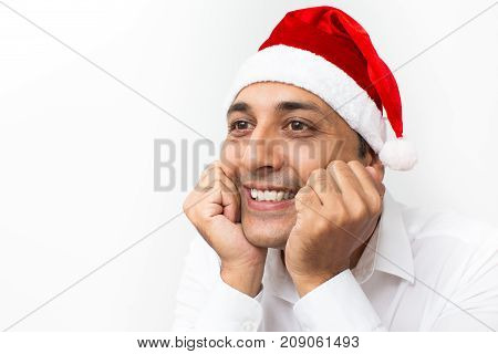 Closeup portrait of dreamy middle-aged handsome man wearing Santa Claus hat, leaning on hands and looking away. Isolated view on white background.