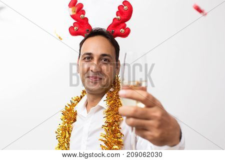Closeup portrait of content middle-aged handsome man wearing toy reindeer horns, tinsel, looking at camera and raising glass with champagne. Isolated front view on white background.