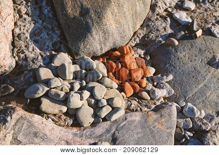Two heaps of sea pebbles stacked together on a stone beach