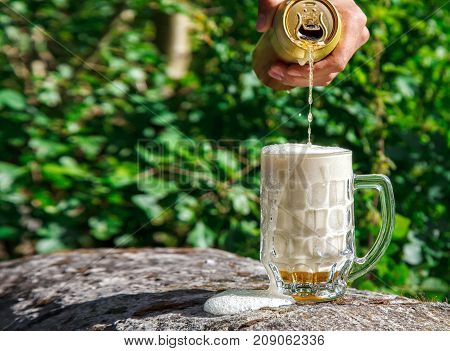 man pouring beer from a jar into a mug in the park on sunny summer day. hand closeup