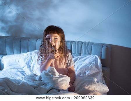 A Girl Of 4 Years Is Screaming Sitting On The Bed In The Night