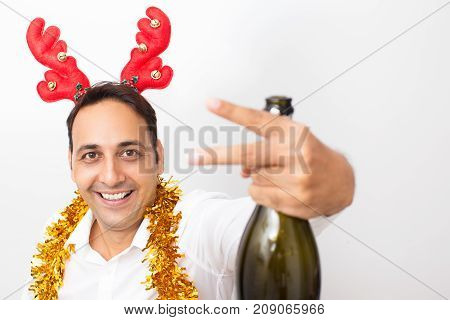 Closeup portrait of smiling middle-aged handsome man wearing toy reindeer horns, tinsel, looking at camera, holding champagne bottle and showing two fingers. Isolated front view on white background.